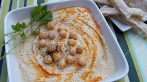 Houmous garnished with chickpeas, olive oil, black pepper and coriander.